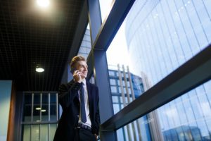 Businessman communicating on cellphone by window of office center